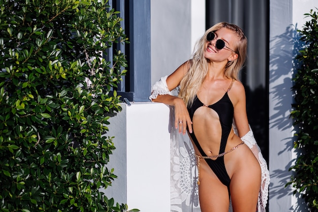 Fashion portrait of young rich stylish european woman in black trendy swimsuit, sunglasses and lace cape outside villa, tropical background, sunset warm light.