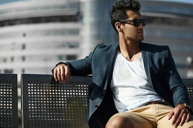 Fashion portrait of young sexy businessman handsome model man in casual cloth suit in sunglasses sitting on a bench in the street