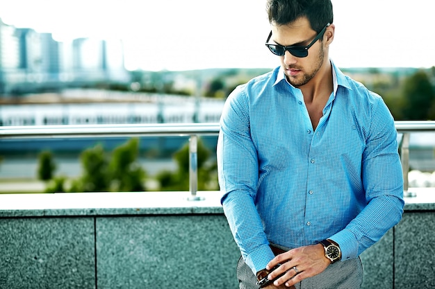 Fashion portrait of young sexy handsome model man in casual cloth in sunglasses in the street