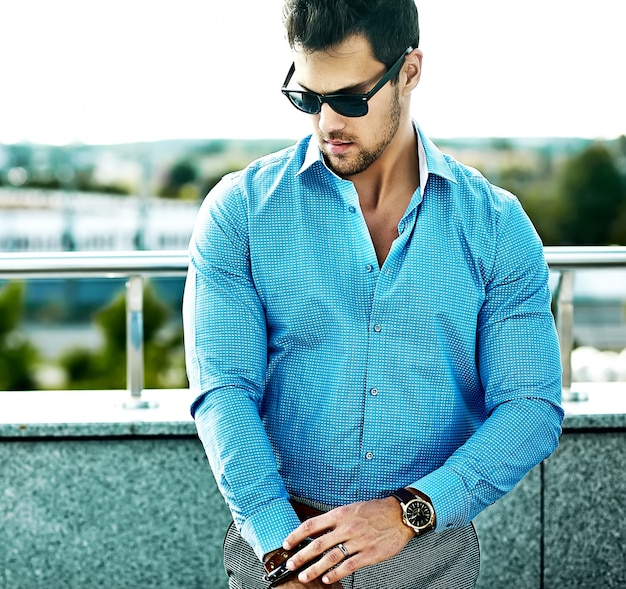 Fashion portrait of young sexy handsome model man in casual clothes in sunglasses in the street