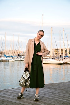 Fashion portrait of young stunning elegant woman posing  promenade, wearing dress coat sneakers and backpack, luxury tourist, soft warm colors.