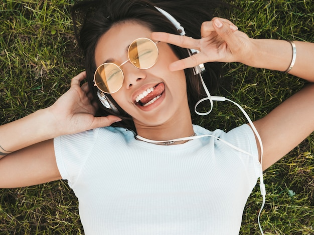 Fashion portrait of young stylish hipster woman lying on the grass in the park .girl weares trendy outfit.smiling model enjoy her weekends. female listening to music via headphones.top view