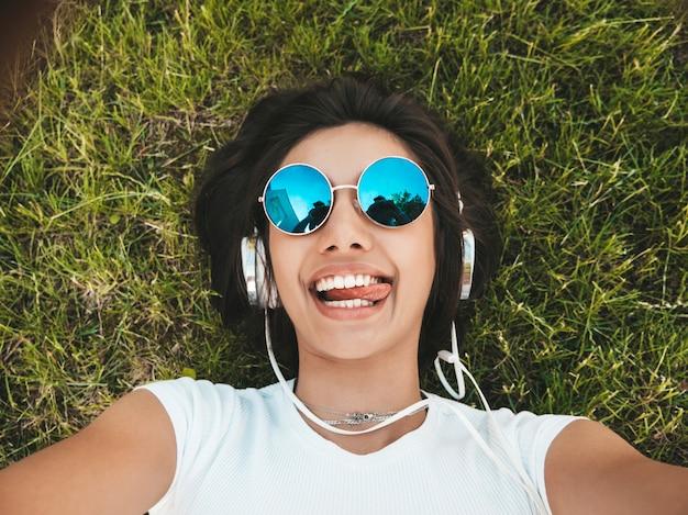 Adatti il ritratto di giovane donna alla moda dei pantaloni a vita bassa che si trova sull'erba nel parco la ragazza indossa l'attrezzatura d'avanguardia selfie di fabbricazione di modello sorridente. donna che ascolta la musica tramite le cuffie. vista dall'alto