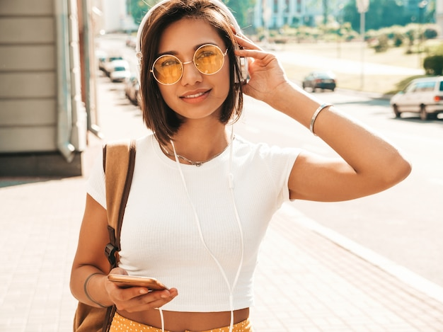 Fashion portrait of young stylish hipster woman walking in the street.girl wearing cute trendy outfit.smiling model enjoy her weekends, travel with backpack. female listening to music via headphones