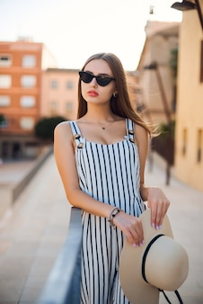 Fashion portrait of young stylish woman walking on the street.