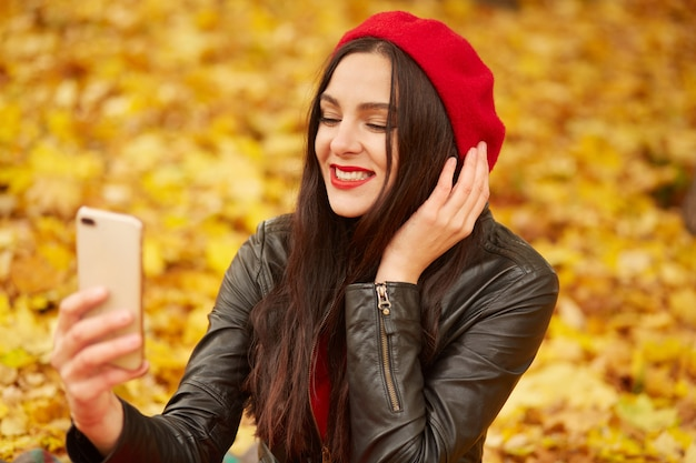 Fashion portrait of young woman outdoor in autumn park or foreest, lady wearing lather jacket, and red beret