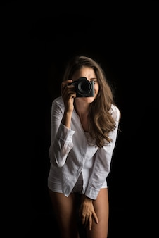Fashion portrait of young woman photographer with camera