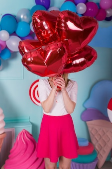 Fashion portrait of young woman in pink dress with an air balloons, candy on a colorful background.
