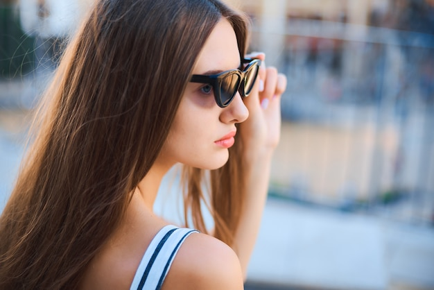 Fashion portrait of young woman sitting and looking into the distance on the street.