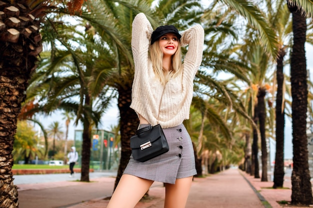 Fashion portrait of young woman wearing, cap, leather jacket, cross body bag, mini skirt, sweater and trendy accessories in promenade