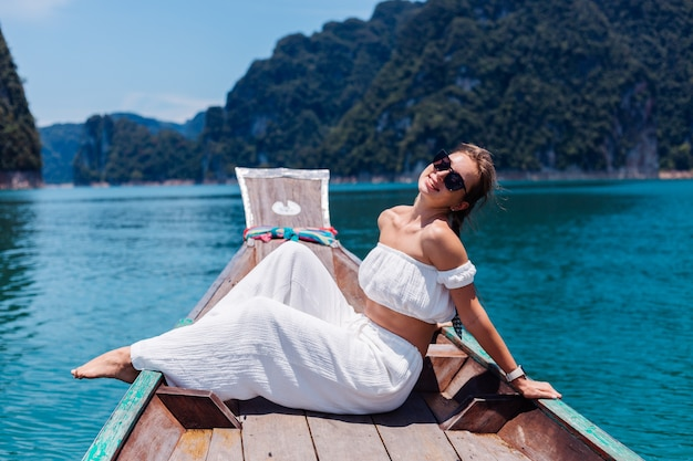 Fashion portrait of young woman in white top and pants on vacation, on sailing thai wooden boat. travel concept. female in khao sok national park.