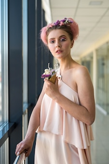 Fashion portrait of young woman with flowers in  mouth