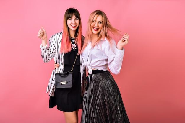 一緒に楽しんでいるカップルの親友の可愛い女の子、エレガントな流行の服やアクセサリー、ピンクの壁のファッションの肯定的な肖像画。