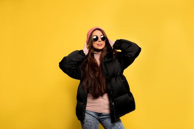 Модная довольно крутая девушка в черной куртке и солнцезащитных очках