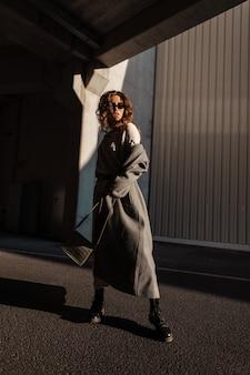 세련된 긴 코트와 가죽 가방에 선글라스를 낀 곱슬곱슬한 여성 모델이 거리를 걷습니다. 어반 여성 캐주얼 스타일