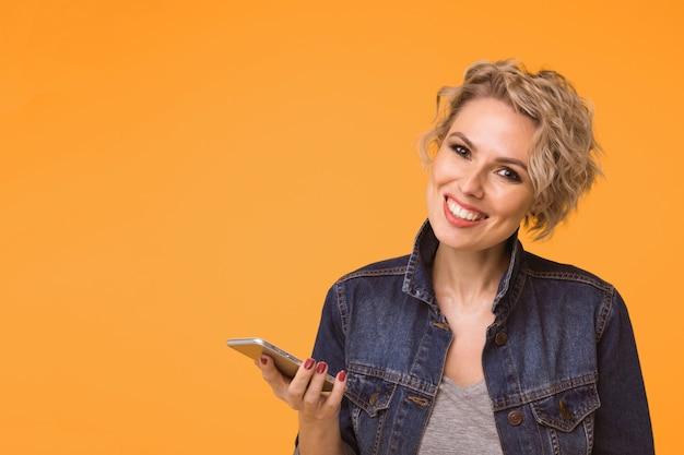 화려한 오렌지 배경 위에 록 블랙 스타일의 스마트 폰을 사용하는 패션 예쁜 여자