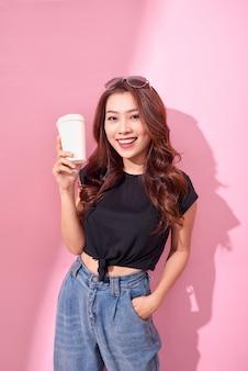 カラフルなピンクの壁に黒い服を着てコーヒーカップとファッションきれいな女性