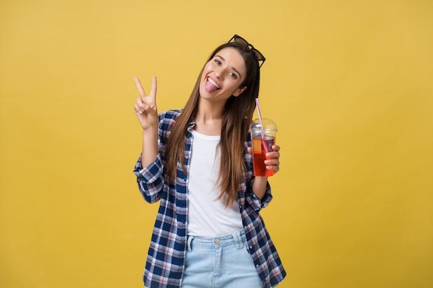 カラフルな黄色の背景の上で楽しんでいる青いシャツの新鮮なフルーツジュースカップを持つファッションかなり若い女性