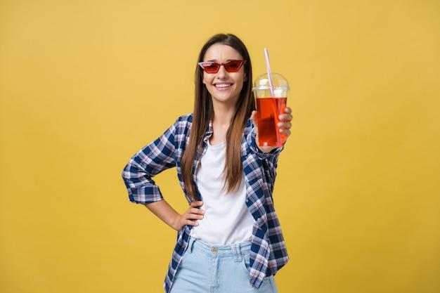 カラフルな黄色の背景の上で楽しんでカジュアルな布で新鮮なフルーツジュースカップを持つファッションかなり若い女性