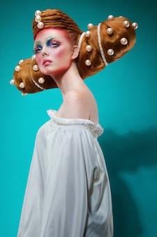 Портрет профиля моды кавказской женщины с творческим красочным макияжем и прической с огромным жемчугом. понятие о парикмахерском искусстве. вертикальный вид.