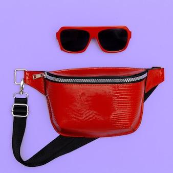 ファッションの赤いクラッチとサングラス。フラットレイスタイル