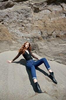 모래 바위 근처 자연에서 포즈를 취하는 패션 나가서는 소녀. 긴 곱슬 머리와 자연스러운 메이크업
