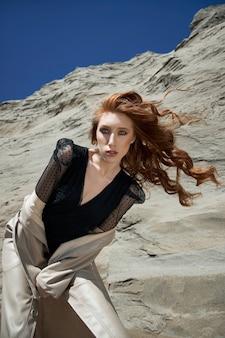 모래 바위 근처 자연에서 포즈를 취하는 패션 나가서는 소녀. 긴 곱슬머리와 자연스러운 메이크업