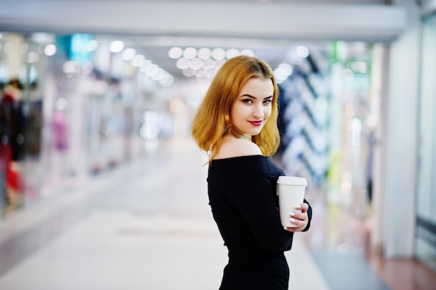 Fashion red haired girl wear on black dress with bright make holding coffee cup at trade shopping center