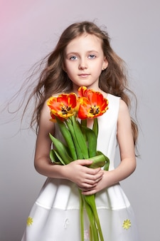 Fashion red-haired girl with tulips in hands. studio photo on light coloured background. birthday, holiday, mother's day, first day of school