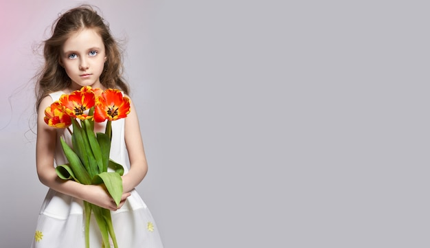 Fashion red-haired girl with tulips in hands.