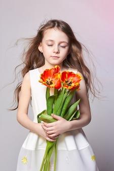 튤립 손에 패션 나가서는 소녀. 밝은 색 배경에 스튜디오 사진입니다. 생일, 공휴일, 어버이날, 개학일