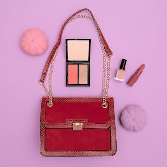 ピンクの背景にファッションの赤い女性のクラッチと化粧品。フラットレイスタイルのコンセプト