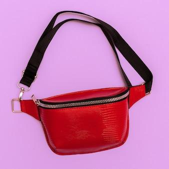 ファッションの赤い女性のクラッチ。フラットレイスタイルのコンセプト