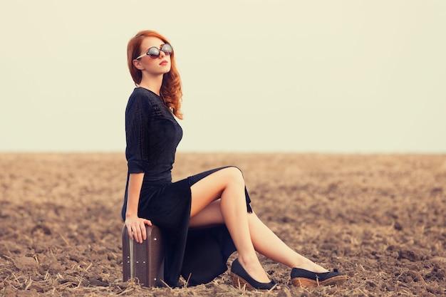 秋のフィールドでスーツケースとファッション赤毛の女性