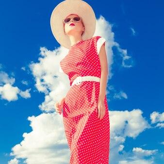 青い空を背景にファッションレトロな女の子