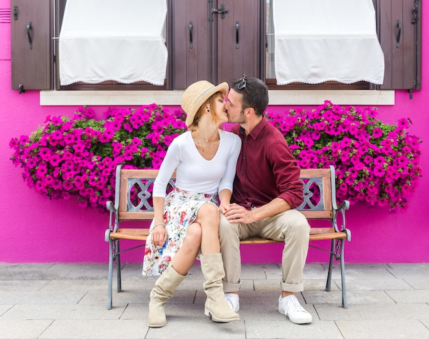 Fashion romantic couple kissing sitting on a bench. purple background color.