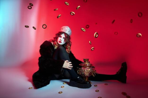 Русская женщина моды в кокошнике с самоваром на красном фоне, яркий макияж, макияж на лице женщины. традиционный русский головной убор, модный современный стиль