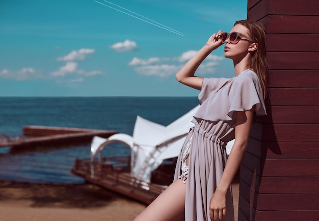 Fashion, seductive girl in knitted swimsuit and pareo