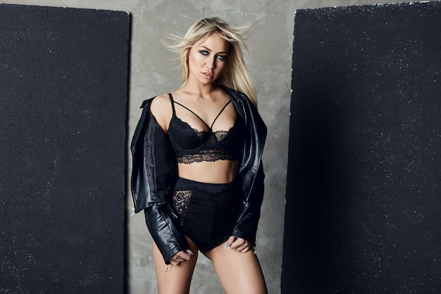 패션 섹시한 금발 검은 속옷과 가죽 재킷 벽 근처에 서있다. 완벽한 몸매와 여성의 큰 가슴, 긴 다리와 머리카락. 집에서 에로틱 한 란제리에 포즈를 취하는 소녀
