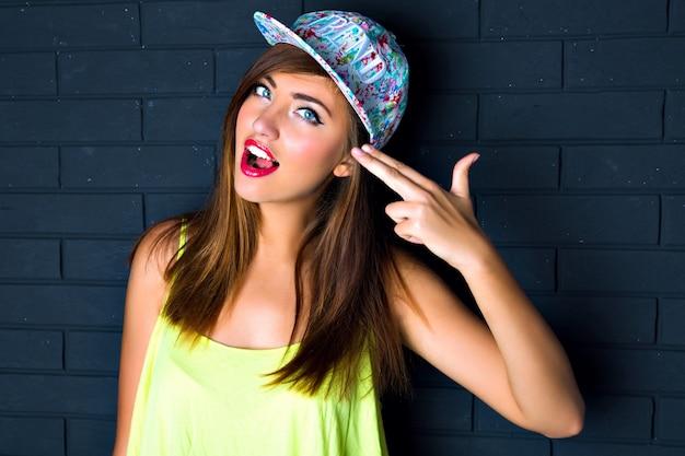 Moda sexy close up ritratto di donna sfacciata, imitando la pistola, mettere la mano sulla testa, labbra carnose sexy, aprire la bocca, cappello luminoso malloppo, stile urbano, muro di mattoni.