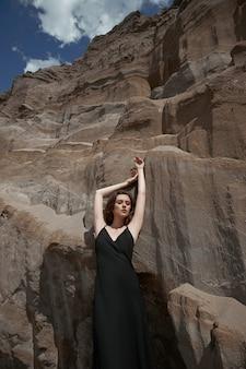 Мода сексуальная женщина в костюме позирует на песчаных скалах. современная независимая девушка, красивый макияж