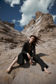 Fashion sexy woman in a suit posing on sand rocks. modern independent girl, beautiful makeup