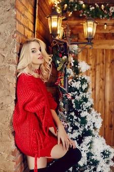 패션 섹시 한 여자 금발 빨간 스웨터, 재미와 크리스마스 트리와 가로등에 대 한 포즈. 마을 집에서 겨울과 크리스마스 트리입니다. 완벽한 몸매와 미소를 지닌 소녀