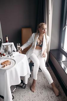Moda giovane donna sexy in abito alla moda in posa seduto al tavolo con cibo e bevande di lusso guardando la finestra. donna seducente glamour in lingerie e abbigliamento elegante che si rilassa godendo di uno stile di vita ricco