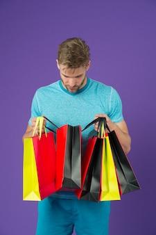 ファッションの買い物客は紙袋を見てください。紫の背景に買い物袋を持つ男。カラフルな紙袋とマッチョ。休日の準備とお祝い。ショッピングまたは販売とサイバーマンデー。