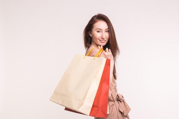 ファッション、ショッピング、人々の概念-白で買い物をした後、紙袋を持つ幸せなブルネットの女性