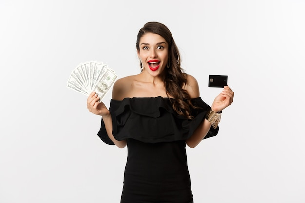 Fashion and shopping concept. excited woman in black dress, showing credit card and dollars, smiling and staring at camera, white background.
