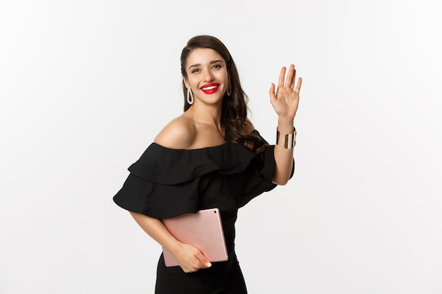 Fashion and shopping concept. stylish young woman with glamour makeup, wearing black dress, holding digital tablet and saying hi, waving hand to greet you, white background