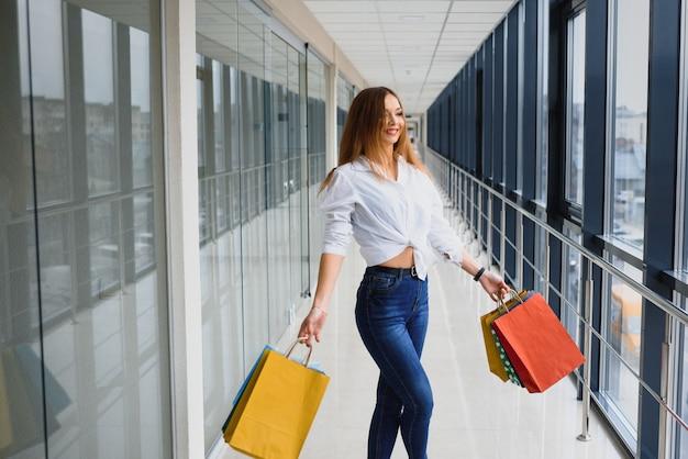 ファッションショッピング少女の肖像画。ショッピングモールで買い物袋を持つ美容女性。買い物客。販売。ショッピングセンター