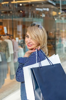 Fashion shopping girl portrait. beauty woman with shopping bags in shopping mall. shopper. sales.